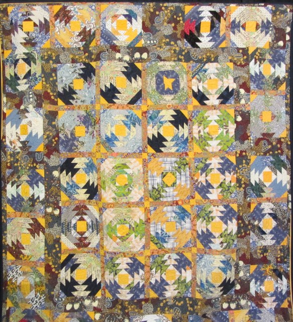 My Best Friend by Nancy Hutchison Scrappy pineapple blocks, created ith fabrics from her late husband's favorite shirts.  Quilting served as therapy following his sudden death.  The backing is an expensive Dallas Cowboy fabric she'd been saving.