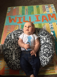 William celebrating his three month birthday on his quilt.